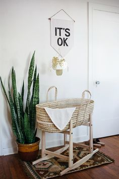 """a little """"nursery"""" for the baby in our bedroom. a rocking moses basket, house plant, and a banner by secret holiday co."""