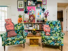 Take a Halloween Home Tour With Jennifer Perkins | HGTV - Pair of floral chairs in front of a gallery wall with oversized Halloween throw pillows.