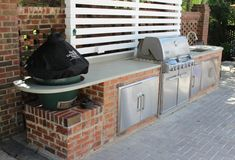 Outdoor kitchen with concrete countertops in Charlotte NC.  The customer wanted the concrete countertops to extend past the brick unsupported.  Only with concrete countertops as strong as ours can you achieve this.  Especially with a large hole in one of the concrete countertop overhangs for the big green egg grill.