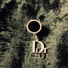 Christian Dior Logo Silver Band Ring with Charm Brand new ring from Dior. A silver band with the logo Dior charm hanging from it. It is marked a sz 6. Brand new. Matches the bracelet I also have listed. Not real silver, more of a costume jewelry line. Dior Jewelry Rings