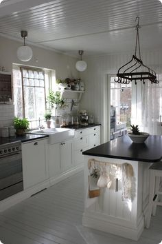 white kitchen, black counter, subway tiles, pot rack