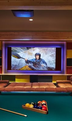 Enormous sectional sofa with ottoman make up this incredible media/games room by Johnston Architects.