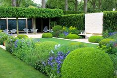 aménagement de jardin et terrasse - végétation abondante, cascade moderne et chaises blanches