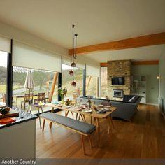 Der Esstisch mit Sitzbänken bildet den Übergang vom Küchen- in den Wohnbereich. Der Parkettboden verbreitet ein Gefühl der Natürlichkeit, das mit dem…