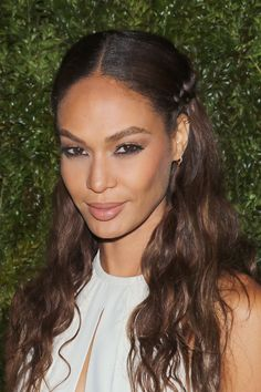Side braids, beach-y waves, and a sleek middle part modernize the model's half up, half down 'do. - ELLE.com