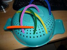 Fine Motor - Lace pipe cleaners in a colander.