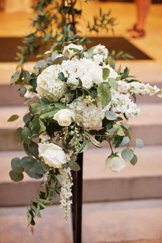 handrail leading up steps to the wimbish house is dressed with white garden roses, white larkspur, white hydrangea, white spray roses, silver dollar eucalyptus, white stock and smilax vines.