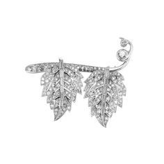 Platinum and Diamond Leaf Brooch/Earclips Combination   Platinum, the stylized pierced leaf earclips, clipped onto a branch, set throughout with 2 round, 12 baguette and numerous single-cut diamonds, circa 1915, approximately 15.4 dwt.