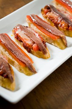 Pictured are two different tapas. One is simply roasted red pepper over a thin angle sliced baguette with an Ortiz anchovy fillet on top drizzled with extra virgin olive