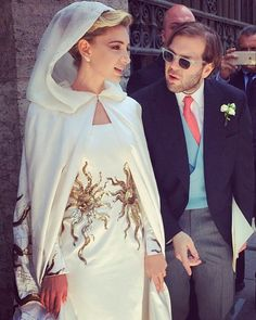 """Wedding Date: May 30, 2015 Groom: Joseph Getty Venue: Basilica of the Twelve Apostles, Rome, Italy For her lavish Roman wedding, the jewelry designer and founder of Sabine G. wore a Schiaparelli Haute Couture gown with a hooded cape embroidered with a golden sun motif by the French house Lesage—who also embellished the bride's Charlotte Olympia heels. """"I wanted something dramatic!"""" she told Vogue."""