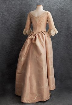 Centennial ball gown. 1876 The grand gown is an amalgam of period features: half 18th century and half Victorian bustle gown. The bodice, reconstructed with Victorian boning and a petersham, retains the original sleeves. The petticoat was remade into the bustle shape.  The gown was made from delicate pale peach taffeta hand-embroidered throughout with ivory silk floss medallions. Some of them which were cut out of extra fabric and appliquéd as borders around the neckline and sleeves.