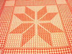 This tablecloth is made of red and white checked gingham and cross-stitched in a large central flower pattern. It is neatly hemmed with the
