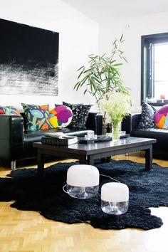 Tummanpuhuvaa olohuonetta koristavat Marimekon värikkäät tyynyt. Seinällä on Fujiwo Ishimoton kankaasta tehty taulu. Mattoliike Helmasta ostetun taljan päällä ovat Harri Koskisen suunnittelemat valaisimet.