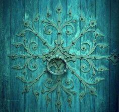 Unique ornamental iron door knocker on a turquoise door