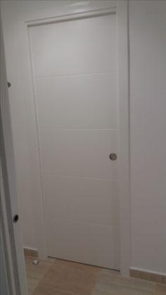 """Puerta corredera maciza lacada en blanco, decorada con cuatro franjas tipo """"pico de gorrión""""."""