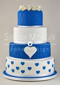 Cobalt Blue and white wedding cake with hearts, quilting, piped vines and white roses.