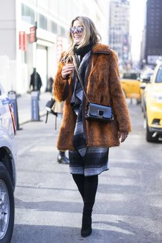 A fur coat layered over a striped dress.