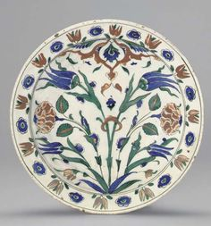 AN IZNIK POTTERY DISH OTTOMAN TURKISH , CIRCA 1590 With sloping rim on short foot, the white interior with a symmetrical design of flaring tulip and rose sprays diverting below an upper red arabesque panel, the rim with alternating blue rosettes and paired red tulips, the exterior with paired blue tulips alternating with green and blue rosettes, cracked, foot ground down and drilled, rim drilled