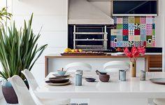 Para compor a área da churrasqueira, a arquiteta Lucilene Leitte escolheu a mesa quadrada e o banco de resina com futon brancos. A brancura do espaço é quebrada pelos azulejos estampados e pela madeira de demolição do tampo da bancada