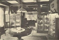 This 1912 view from the Dining Room looks through a Colonnade to the Living Room. Wainscot paneling is in the Dining Room, but not the Living Room. The woodwork is stained and either varnished or shellacked fir. Built-in China cupboards have leaded-glass doors. The simple curtains are lace, with dark green roller blinds behind for nighttime privacy and draft exclusion.