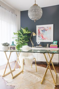 """A chic and glam office: One Kings Lane 6'x7'6"""" dyed devore hide, West Elm credenza, fiddle leaf tree, and gold framed glass table."""