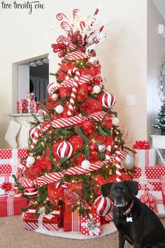 Red and white Christmas tree with candy cane striped ribbon, red mesh ribbon, ornaments, and red and white wrapped Christmas gifts.