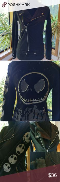 EUC Jack Skellington moto hoodie Bought in Walt Disney World by the Haunted Mansion.  Great condition, no holes or stains. Just one loose thread on sleeve (see photo collage, bottom right), minor cracking on foil Jack faces. Thumb holes, Jack face snap buttons throughout on sleeves and collar, foil silkscreening, Jack face zipper pull. Fitted,  size medium but runs small. Nightmare Before Christmas,  Tim Burton, punk, Hot Topic. Disney Tops Sweatshirts & Hoodies