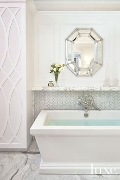 Spa like bathroom features modern freestanding bathtub paired with wall-mounted tub filler mounted ...