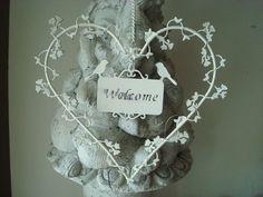 """Suspension en forme de coeur champêtre avec en son centre un panonceau ajouré """"Welcome"""", elle est réalisée en métal blanc réhaussée de deux oiseaux, à suspendre partout dans la maison pour une déco coeur pleine de charme.    Dimensions : 16 cm x 16 cm"""