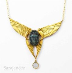 Egyptian Revival necklace, scarab with winged uraei on either side, gold-tone metal and glass, French, 1920s.