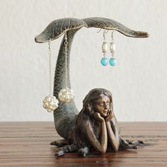 [orginial_title] – Touch of Class Mermaid Figurine Tabletop Earring Holder This dreamy Mermaid helpfully holds your earrings as you decide on the perfect outfit. This tabletop earring holder is hand-painted with a verdi patina tail. Mermaid Home Decor, Mermaid Bedroom, Mermaid Jewelry, Mermaid Art, Mermaid Sculpture, Mermaid Mermaid, Keramik Design, Jewelry Holder, Earring Holders