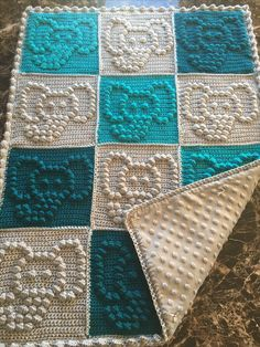 Crocheted baby blanket in teal, turquoise and gray backed with velvet fleece