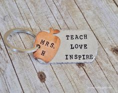 "TEACH LOVE INSPIRE  Personalize this Silver Aluminum key chain with name of your favorite teacher!  An 18 gauge Aluminum, Military style dog tag Measuring 2"" x 1.10""  is hand stamped with ""teach love inspire"". The edges are hammered for a more rustic look. I add an apple stamped wit..."