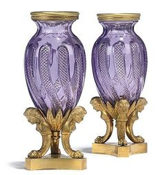 A PAIR OF RUSSIAN ORMOLU AND AMETHYST CUT-GLASS VASES <br />CIRCA 1840-1850 <br />Each with spirally decorated ovoid body supported by maiden-headed monopodia with paw feet, on a concave-sided plinth<br />7½ in. (19 cm.) high (2)<br />