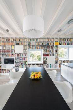 This dining space features a view of the floor-to-ceiling bookshelf and the garden.