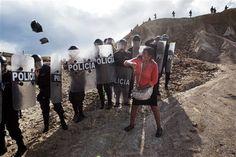 Uma mulher joga uma pedra e um saco em policiais de choque que bloqueiam seu caminho de casa no distrito de Huepetuhe em Madre de Dios região do Peru, no Peru, de segunda, 28 de abril de 2014. Soldados, policiais e fuzileiros navais começaram destruindo ilegal de máquinas de mineração de ouro no sudeste do Peru região de selva de Madre de Dios.  As autoridades começaram a impor uma proibição de mineração ilegal segunda-feira no distrito Huepetuhe.  Antes do prazo, os mineiros entraram em…