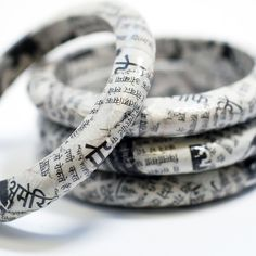 Recycled newspaper bangles by SquishySushi on Etsy — but could be DIY.