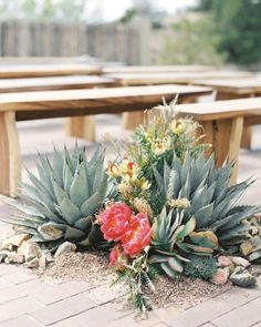 The outdoor aisle at this Sante Fe wedding was lined with clusters of succulents, coral peonies, and ranunculus that fit the event's peach-and-green palette.