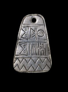 Flat sheet-silver amuletic pendant; pierced at the top to form a circular perforation for suspension; engraved Sabaean inscription in South Arabian script; jagged line decoration at the bottom; plain reverse, with circular impression around the perforation, possibly from contact with another object.