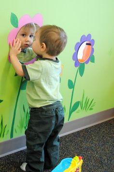 Je hangt allerlei spiegels op aan de muur op verschillende hoogtes. Nadien ga je het kind laten recht staan en naar zichzelf laten kijken in de spiegels.Bij dit spel gaan we vooral het recht staan van het kind stimuleren(grove motoriek).