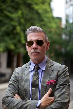 Camoillionaire, Nick Wooster perfects this camo-chic look by pairing together a vintage washed woodland print blazer, matching tie, and a deal-sealing accenting red bandana.
