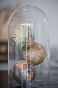 Globes under a glass cloche. Cloches in store only.. Globes are online now.