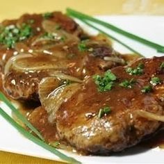 Hamburger Steak with Onions and Gravy - An easy-to-make classic featuring tasty hamburger 'steaks' smothered in gravy and onions. Traditionally served with hot white rice or potatoes, it's a great way to dress up a pound of ground beef and you probably have all the ingredients on hand,,