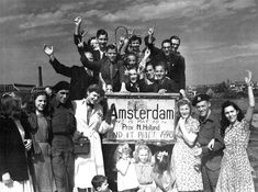 Recently liberated Dutch civilians and Canadian soldiers pose with a sign in Amsterdam indicating that the city had been liberated after almost five years