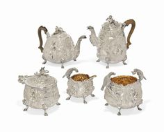 A GEORGE III SILVER FIVE-PIECE TEA AND COFFEE SERVICE MARK OF EDWARD FARRELL, LONDON, 1816/17 Profusely chased in relief with a man in 17th century dress, with clay pipe, seated in woodland setting with windmill, buildings and a barrel hanging by rope from a branch, to one side, the other side with Jupiter, holding sceptre and lightning bolt, his sacred bird, the eagle forming the handles of the cream jug and sugar bowl, gilt interiors, teapot and coffee pot with wooden handles, elaborate…