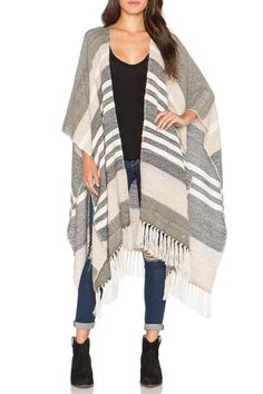 Mixed neutral stripes adorn this oversized poncho cape with fringe detailing on hemlines. Each piece is made by hand in Peru out of eco-friendly Alpaca fur. Throw this piece over all of your favorite winter basics and a great pair of jeans and boots. Belt this piece in the front to add a little more definition to your shape.   Poncho Cape by Ayni. Clothing - Sweaters - Ponchos & Capes Wicker Park, Chicago, Illinois