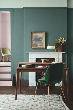 Green velvet chair and dark green walls.