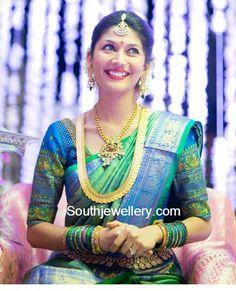 Kanjivaram Silk Saree in Shades of Blue and Green with Gold Jewelry