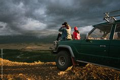 old jeep parked in the wild area surrounded by mountains by Nikolay Bondarev for Stocksy United