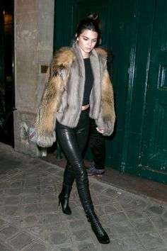 The model takes a break from her Paris Fashion Week duties and heads out to dinner wearing a Sally LaPointe fur coat and leather leggings with lace-up Balmain booties.